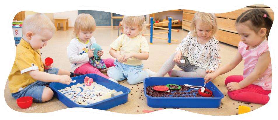 group of preschoolers playing in sensory bins